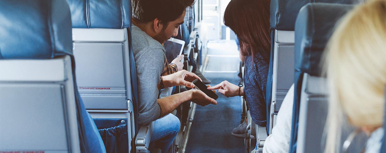 Młoda para używająca telefonu komórkowego podczas lotu.